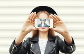 Fashion woman makes selfie on smartphone view of screen
