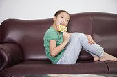 Portrait of a girl sitting on a couch and licking a lollipop
