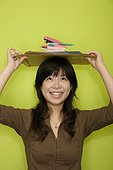 Young woman carrying office stationeries on her head and smiling