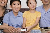 Mature couple with their children playing video game