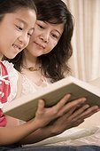 Girl sitting with her mother and reading a book