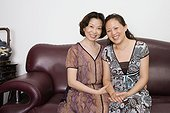 Portrait of two mature women sitting on a couch and smiling