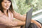Young woman looking at a laptop and smiling