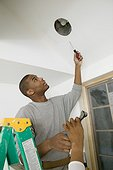 Male carpenter changing a lightbulb