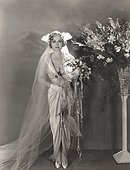 Bride standing next to tall vase of flowers
