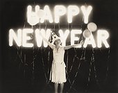 Woman standing in front of neon Happy New Year sign