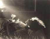 Sunlight falling on woman with flowers sleeping in bed