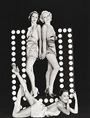 Three models posing by large letter U