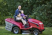 Toddler with father on lawnmower
