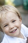 Smiling blond girl outdoors, portrait