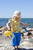 Little girl with watering can at the ocean