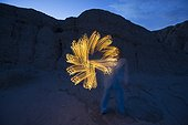 Adult woman creating a flower like shape with a flashlight while she lightpaints at night in the Anza Borrego Desert State Park, California.