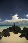 Man sitting on rock at beach and looking at view of ocean, Marley Beach, Bermuda