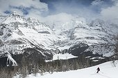 Scenery with mountains and person skiing in winter near Lake O Hara, Yoho National Park, British Columbia, Canada