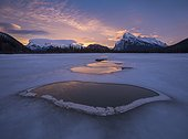 Frozen Vermilion Lake with thawed ice patches in winter at sunrise, Banff National Park, Alberta, Canada