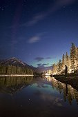 Aurora Borealis at night over lake with silhouette of man standing on shore, Banff National Park, Alberta, Canada