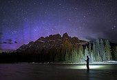 Man fishing in lake at night near Castle Mountain, Banff National Park, Alberta, Canada
