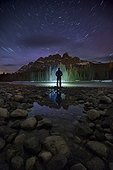 Man standing on lakeshore at night near Castle Mountain, Banff National Park, Alberta, Canada