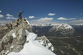 Mountain climber at summit of Mount Rundle, Banff National Park, Alberta, Canada