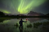 Aurora Borealis over photographer with tripod in lake and mountains in Banff National Park, Alberta, Canada
