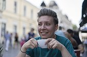 Teenage woman traveling through Central Europe having a coffee at an outdoor cafe.