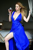 Glamours sexy young woman standing wearing blue dress and holding a glass of wine looking at the far distance from her bedroom and day dreaming.