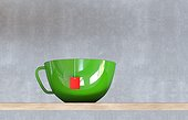 Close-up of a green cup of tea, with a red teabag-label, sitting on a wooden table against a concrete wall