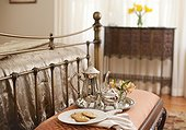 Silver set and cookies on bench at end of bed in bedroom, Mount Merino Manor, Hudson, New York