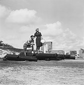 Young couple standing on cannon, smiling