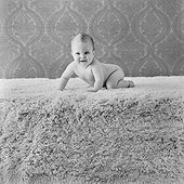 Baby boy crawling on rug, smiling