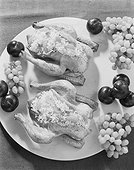 Stuffed chicken and fruits in plate, close-up