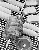 Spit roasting of ham on barbecue grill with corn cobs, close-up