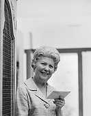 Senior woman holding letter, smiling, portrait