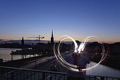 Person drawing light heart shape in air, Stockholm, Sweden