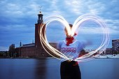 Person drawing light heart shape in air, Stockholm City Hall in background, Sweden
