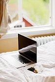 Laptop and hotel key on bed, Sweden