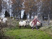Girl walking, sheep in background, Smaland, Sweden