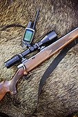 Hunting riffle with sighting telescope and walkie-talkie with wild boar in background
