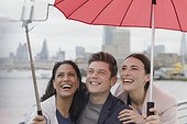 Smiling friend tourists with umbrella taking selfie with selfie stick, London, UK