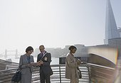 Business people using digital tablet at sunny urban waterfront, London, UK