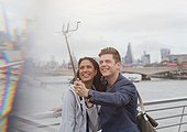 Couple tourists taking selfie with camera phone selfie stick at Thames River waterfront, London, UK