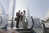 Business people with suitcase using digital tablet on sunny waterfront, London, UK