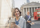 Portrait smiling businesswoman texting with cell phone on urban city street, London, UK