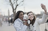 Playful, smiling lesbian couple with white dog taking selfie with camera phone in urban park, London, UK