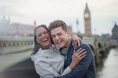Portrait enthusiastic, laughing couple tourists standing at Westminster Bridge, London, UK
