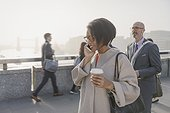 Silhouette businesswoman talking on cell phone and drinking coffee on urban bridge, London, UK