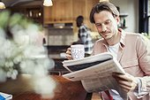 Man drinking coffee and reading newspaper in kitchen