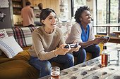 Laughing women friends playing video game on living room sofa