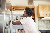 Woman reaching into refrigerator in kitchen