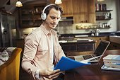 Man with headphones working at laptop, reading paperwork in kitchen